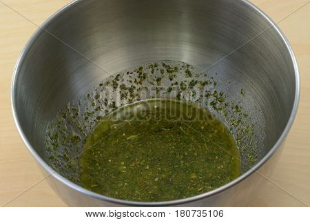 Close up of homemade salad dressing with herbs in stainless steel mixing bowl