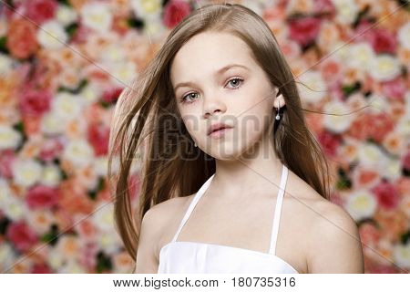 Close up portrait of a beautiful little girl in white dress in a studio on a floral wall background