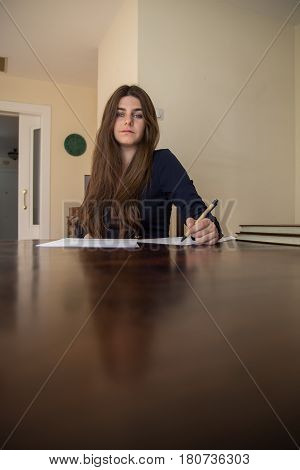 Pretty young woman with blue eyes and brown hair sitting on an elegant wooden table typing on a blank sheet in the living room of her house. She is working and dressed smartly.