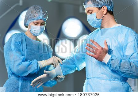 Attentive nurse is helping surgeon to wear white rubber glove. They standing at operating-room. Low angle