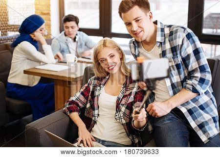 Share emotions. Cheerful young students making selfies while their groupmates studying in the background