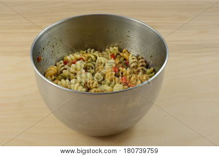 Vegetable rotini pasta salad with herb spice salad dressing in stainless steel mixing bowl