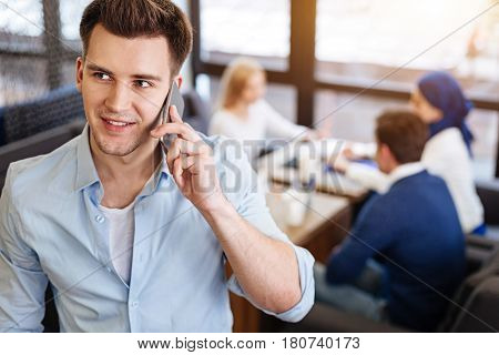 Talk over and over. Cheerful handsome young man talking on cellphone and smiling while his colleagues sitting in the background in the cafe