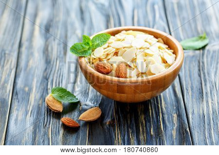 Almond Flakes And Whole Almonds In A Wooden Bowl.