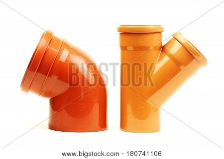 Composition from red plastic sewer pipes, isolated on white