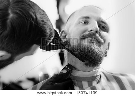 Cut your mustache in the barbershop. Barber shave the beard of the client with trimmer Men's hairstyling and haircutting in a barber shop or hair salon. Grooming the beard.