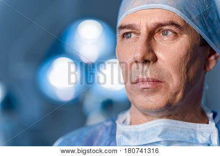 Despondent surgeon in cap and protective wear is looking aside. Portrait
