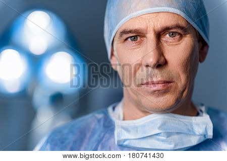 Disheartening male surgeon is looking at camera with despondence. Portrait. Copy space