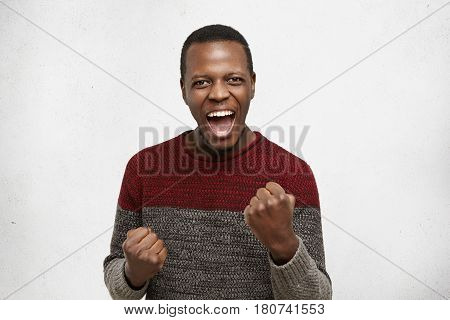 Human Emotions And Feelings. Happy Lucky Excited Young Dark-skinned Male Winner Exclaiming, Rejoicin