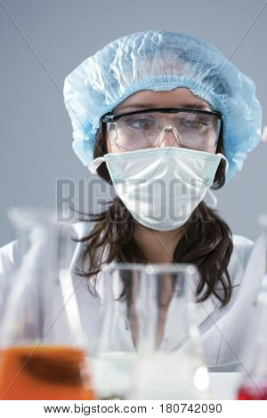 Researching Ideas and Concepts. Female Laboratory Assistant in Facial Mask And Protective Gloves During Scientific Experiment With Micro Cells.Vertical Image Composition