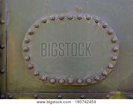 Metal plate inspection hatch on the side of a vintage steam train blank with space for text. Oval shape surrounded by nuts and bolts.