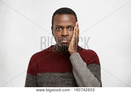 Indoor Portrait Of Funny Bug-eyed Forgetful Young African American Man Dressed In Casual Sweater Hav