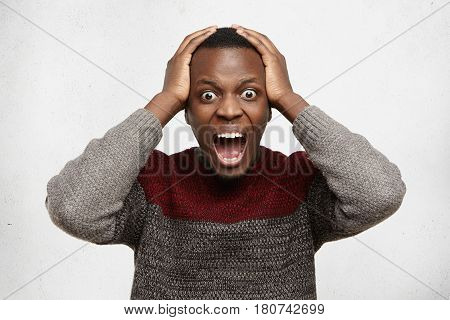 Stressed And Shocked Young African American Student Holding Hands On His Head And Shouting, Keeping