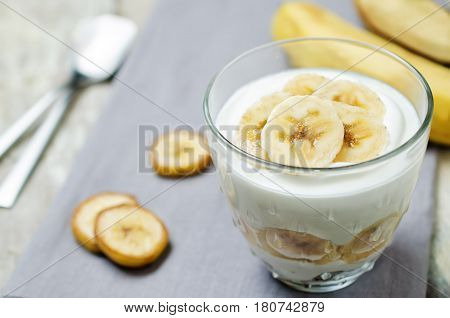 Greek yogurt banana parfait on a wood background.