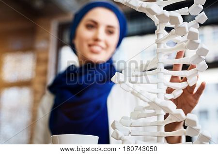 New prospective. Selective focus of DNA model with muslim woman learnign it in the background
