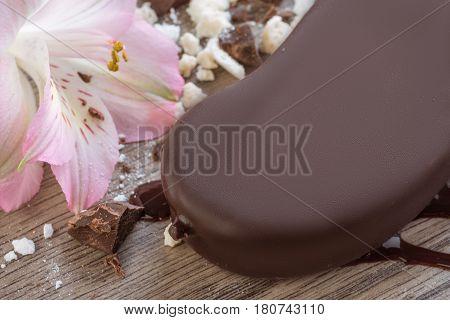 tasty sundae in milk chocolate with flower on wooden background