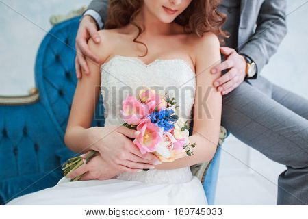 Bride in beautiful dress and groom in gray suit sitting on sofa indoors in white studio interior like at home. Trendy wedding style .Wedding