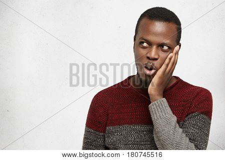 Shocked Or Surprised Young Handsome African American Man Exclaiming In Astonishment, Keeping Hand On