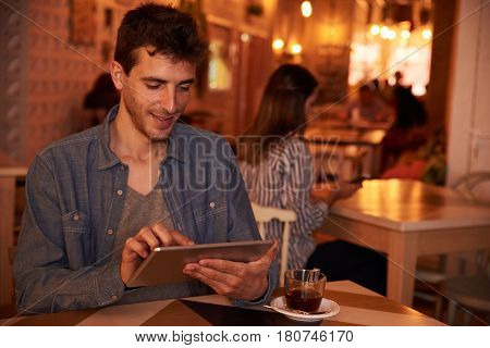 Happily Typing Young Man In Restaurant