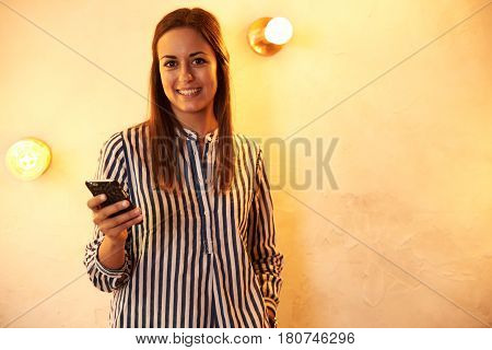 Millennial With Cellphone Smiling At Camera