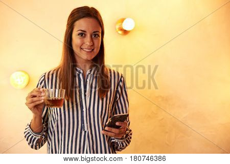 Posing Woman With Tea And Cellphone