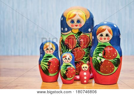 Set of Russian dolls standing next to a wooden table
