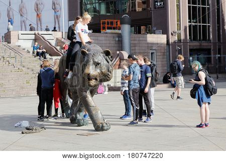 Oslo Norway - September 16 2016: Teenagers riding and are near the Tiger (Tigeren) made by Elena Engelsen in front of the Oslo Central station at the square Jernbanetorget i downtown Oslo Norway.