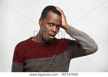 Forgetful And Clueless Young African American Male Dressed In Casual Sweater Opening Mouth In Shock