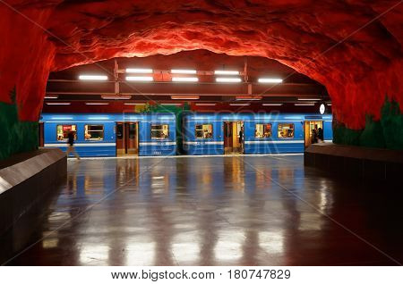 Solna Sweden - June 6 2016: One blue subway train in service for the Stockholm metro system has stoped and has open doors at the underground station Solna Centrum cave like metro station.