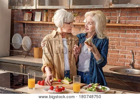 Happy female senior friends are cooking healthy food together. They are standing and embracing. Lady is eating sandwich and smiling