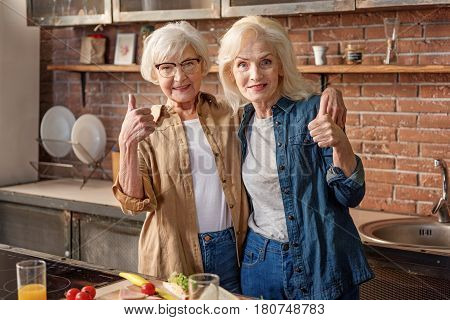 Everything is okay. Joyful two old women are giving thumbs up and embracing. They are standing in kitchen and smiling