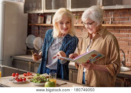 Lets cook something delicious. Joyful female senior friends are looking at recipe book with excitement. They are standing in near healthy food on table and smiling