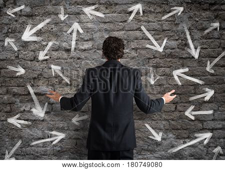 Confused businessman looking a wall with directional arrows
