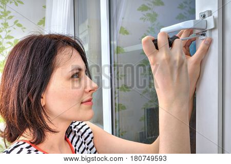 The girl dismantles the window handle using a screwdriver.