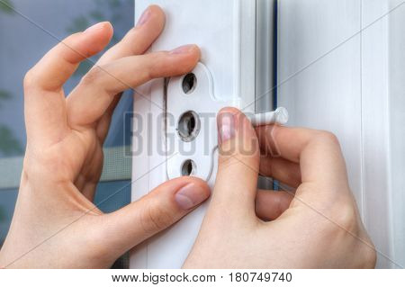 Close-up of the hand of a locksmith installing a window limiter on a plastic frame.
