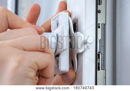 Installer hands close-up installation of limiter pvc window.