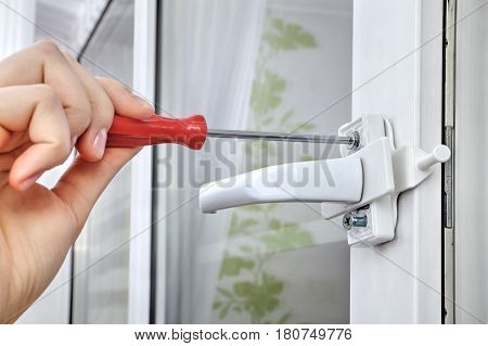 Installation of window restrictor to windows using your hands close-up.