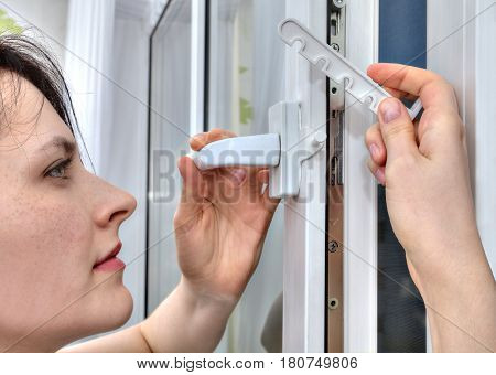 The girl mounts the tilt and turn stopper on the plastic window.