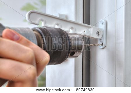 Drilling holes for fasteners to install the window limiter close-up.