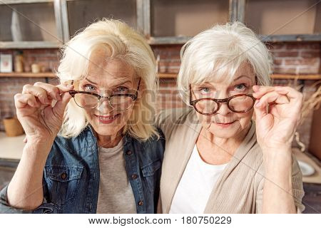 We see you. Portrait of curious two old women are touching their eyeglasses and looking forward with interest. They are standing in kitchen and embracing