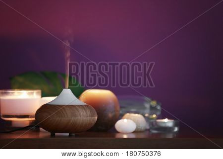 Aroma oil diffuser and candles on table