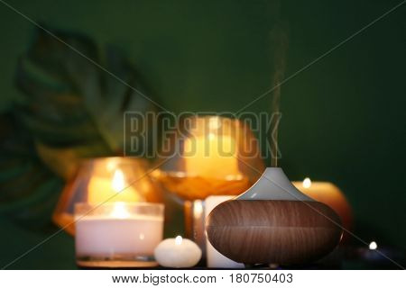 Aroma oil diffuser on blurred candles background