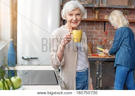 Portrait of happy senior woman drinking cup of tea and smiling. She is standing and looking at camera with joy. Her friend is cooking on background