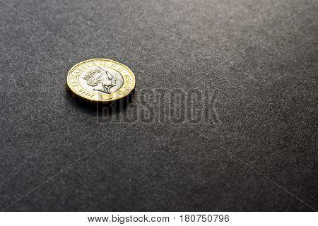 New british one sterling pound coin on dark background.
