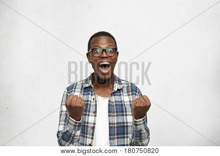 Omg! Portrait Of Shocked And Amazed Young African Man In Stylish Clothing Clenching Fists And Scream