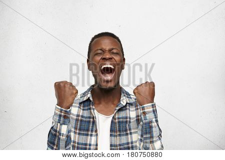 Emotional Successful Lucky African American Man Screaming With Mouth Wide Opened And Eyes Closed, Cl