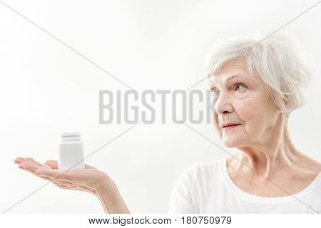 Secret of my health and longevity in this medicaments. Portrait of confident old woman is stretching hand aside and holding jar of vitamins. Isolated
