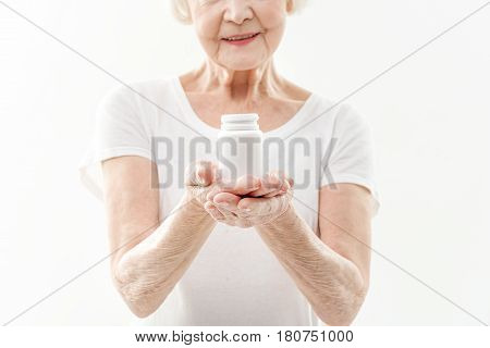 Kind old lady is presenting pills in her hands. She is standing and smiling. Focus on jar. Isolated