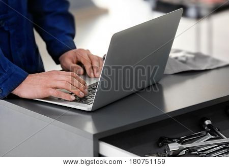 Auto mechanic working with laptop in car repair shop, closeup