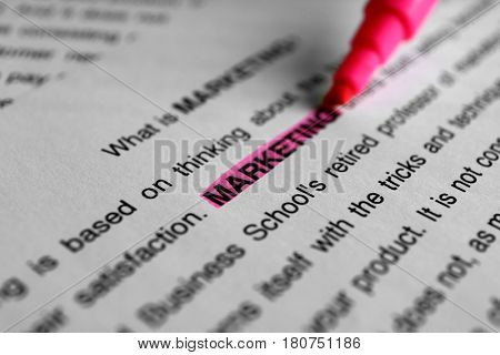 Highlighting word MARKETING on paper sheet using felt pen, closeup